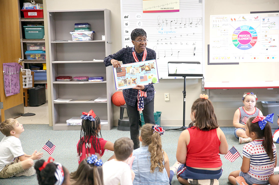 "MUSIC TEACHER GLORIA SCOTT Richmond teaches students the history of the National Anthem on ""Star-Spangled Banner"" Day. Richmond is celebrating her 30th year as an educator this year."