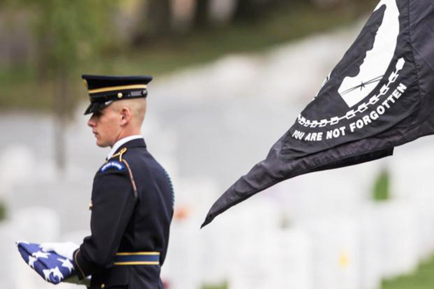 A MEMBER OF THE U.S. Army's 3rd U.S. Infantry Regiment (The Old Guard) holds an American flag as he stands next to the POW/MIA flag before a service for U.S. Army Cpl. Robert E. Meyers of Greencastle, Pa. Meyers was a soldier who went missing in the Korean War, whoseremains have been identified due to advances in technology. His remains were buried in 2015, at Arlington National Cemetery in Arlington, Va.