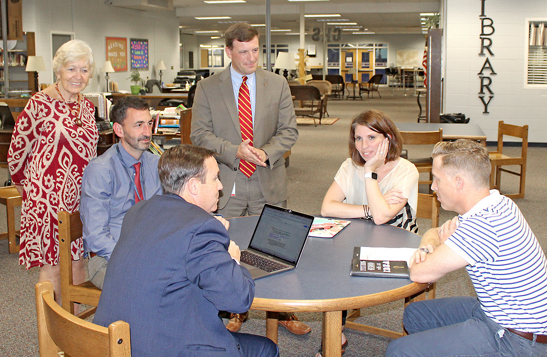 CLEVELAND DIRECTOR of Schools Dr. Russell Dyer, standing center at the rear, looks over a discussion group at Thursday night's Strategic Planning Session in the Cleveland High School Library. At the table, from left, are Board of Education member Carolyn Ingram, school administrators Michael Kahrs and Jeff Elliott, and parents Dana Storey and Chad Higgs.