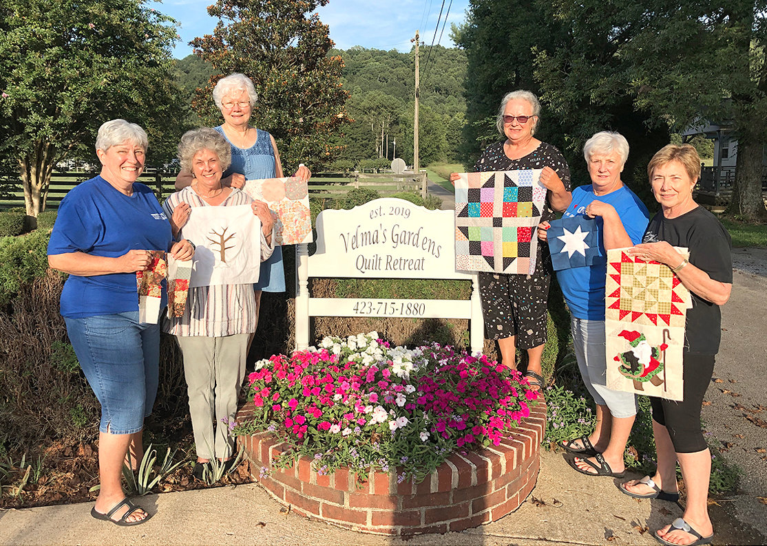 PARTICIPANTS in Velma's Garden Quilt Retreat open house hold up their creations by the new business's sign on Godfrey Lane in Cleveland.