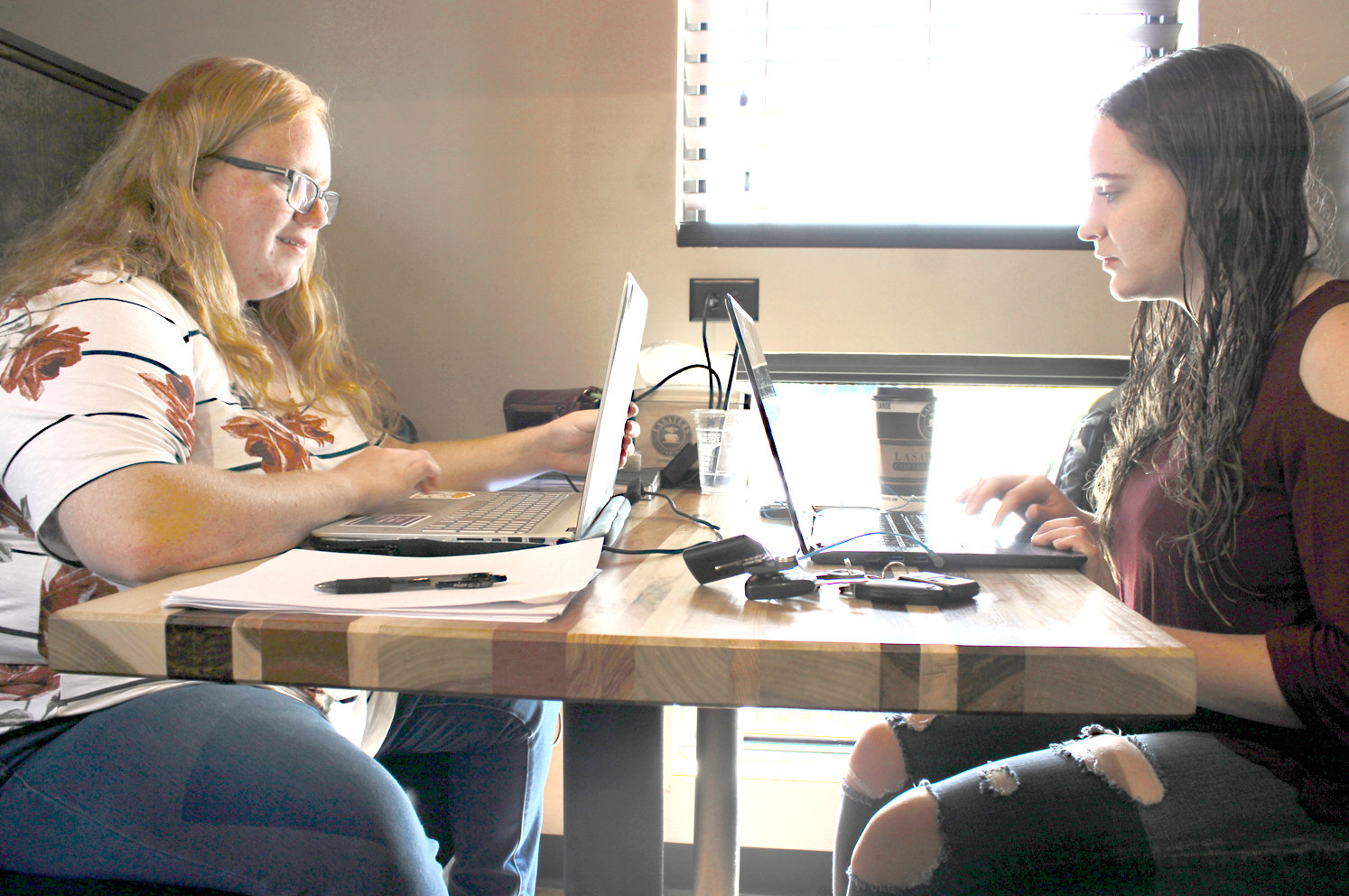 LEE UNIVERSITY STUDENTS Chelsa Flanary and Miranda Sawyer connect to the Wi-Fi at Lasater's Coffee and Tea to work on their assignments during cafe hours. While not the case for these students, many local residents struggling to afford expenses like internet service at home get their internet access at public places like libraries and cafes.