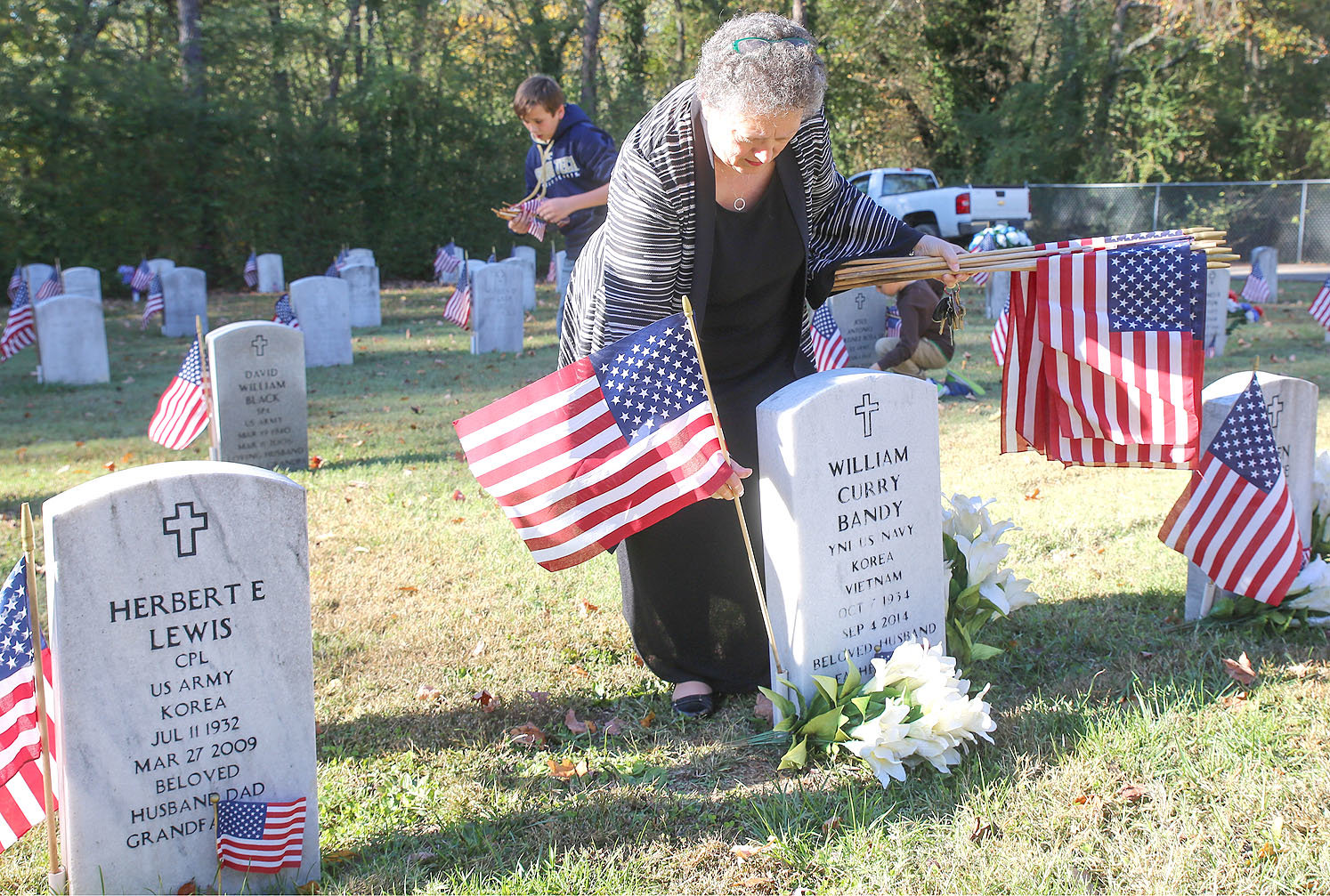ANITA GREEN places a flag beside a headstone at the Fort Hill Veterans Cemetery. She was one of many local volunteers who worked with AmVets and local veteran organizations to decorate the local Veterans Cemetery in advance of Veterans Day.