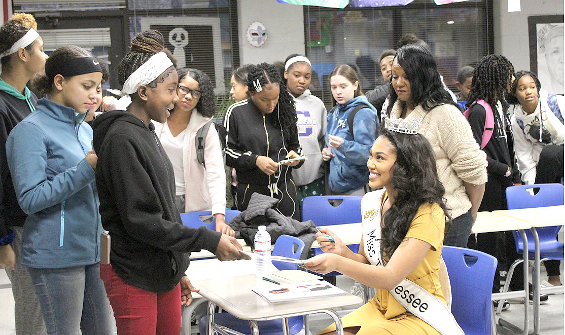 MISS TENNESSEE 2019, Brianna Mason, seated, was busy autographing photographs for students in the Cleveland Middle School Mentee Program Friday morning. The program is sponsored by the 100 Black Men of Bradley County.