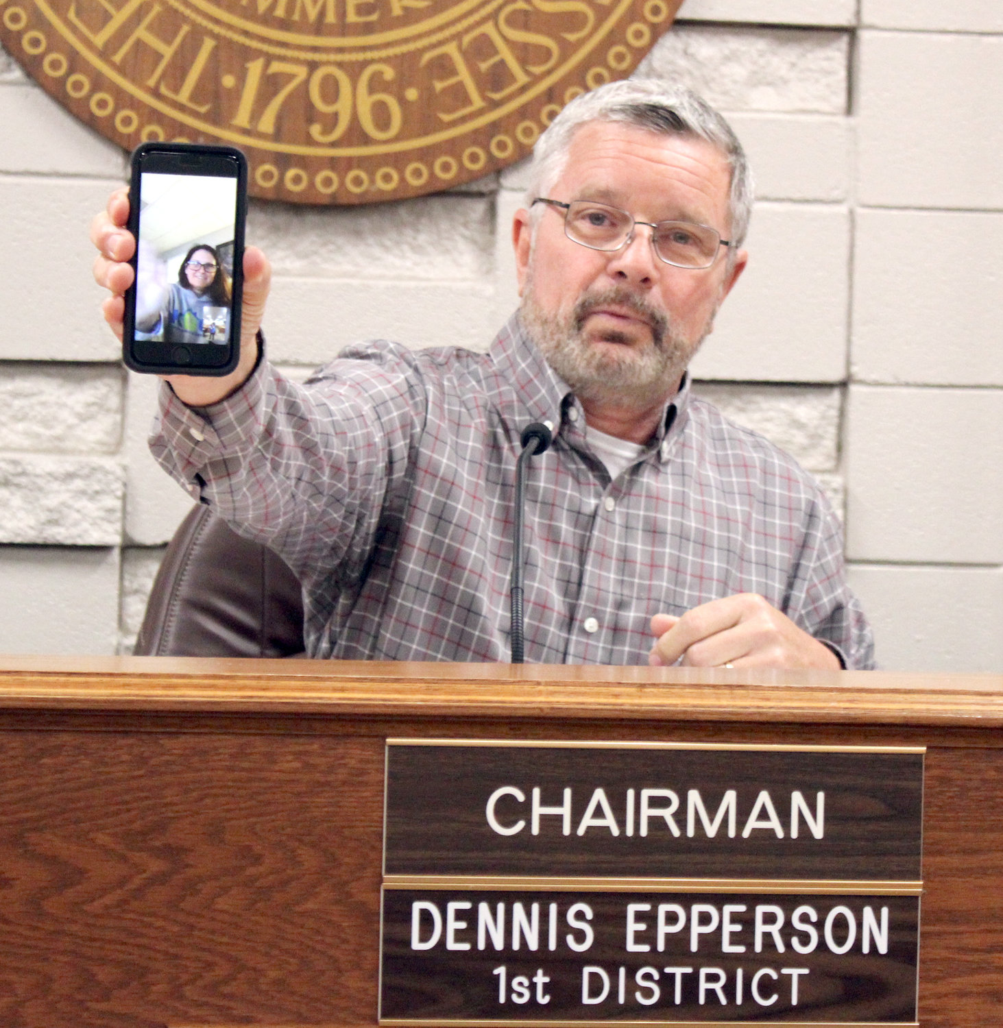 BRADLEY COUNTY Commissioner Charlotte Peak is shown waving on a smartphone screen held by IT Committee Chairman Dennis Epperson, during Monday's meeting. Peak later joined a call with three other commissioners on another smartphone, so everyone joining the meeting remotely could see each other.