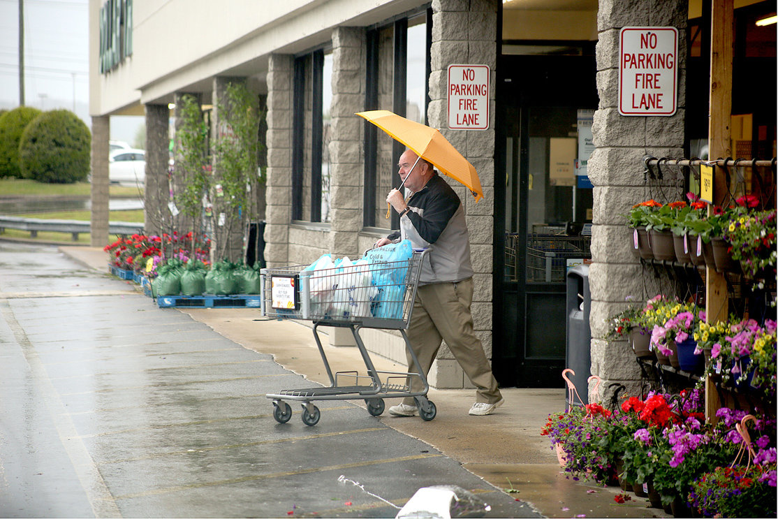 USING AN UMBRELLA in Tuesday morning's rain, a Cleveland shopper makes his way to his car after loading up on groceries and other items. Most local grocers believe the rush that has emptied their shelves is beginning to subside.