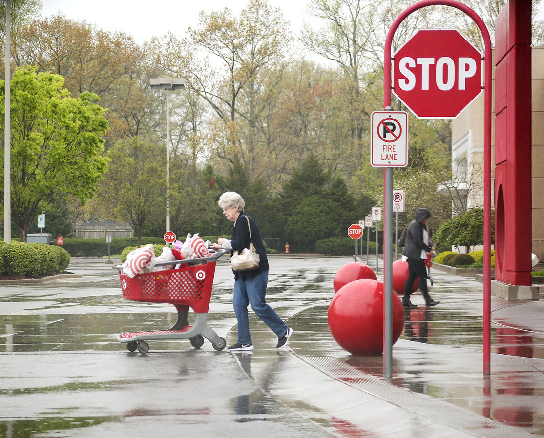 A SHOPPER braves the rain as she leaves Target on Tuesday morning. Although the demand on grocery shelves is lessening, store managers still report problems in keeping certain items stocked, especially toilet paper.