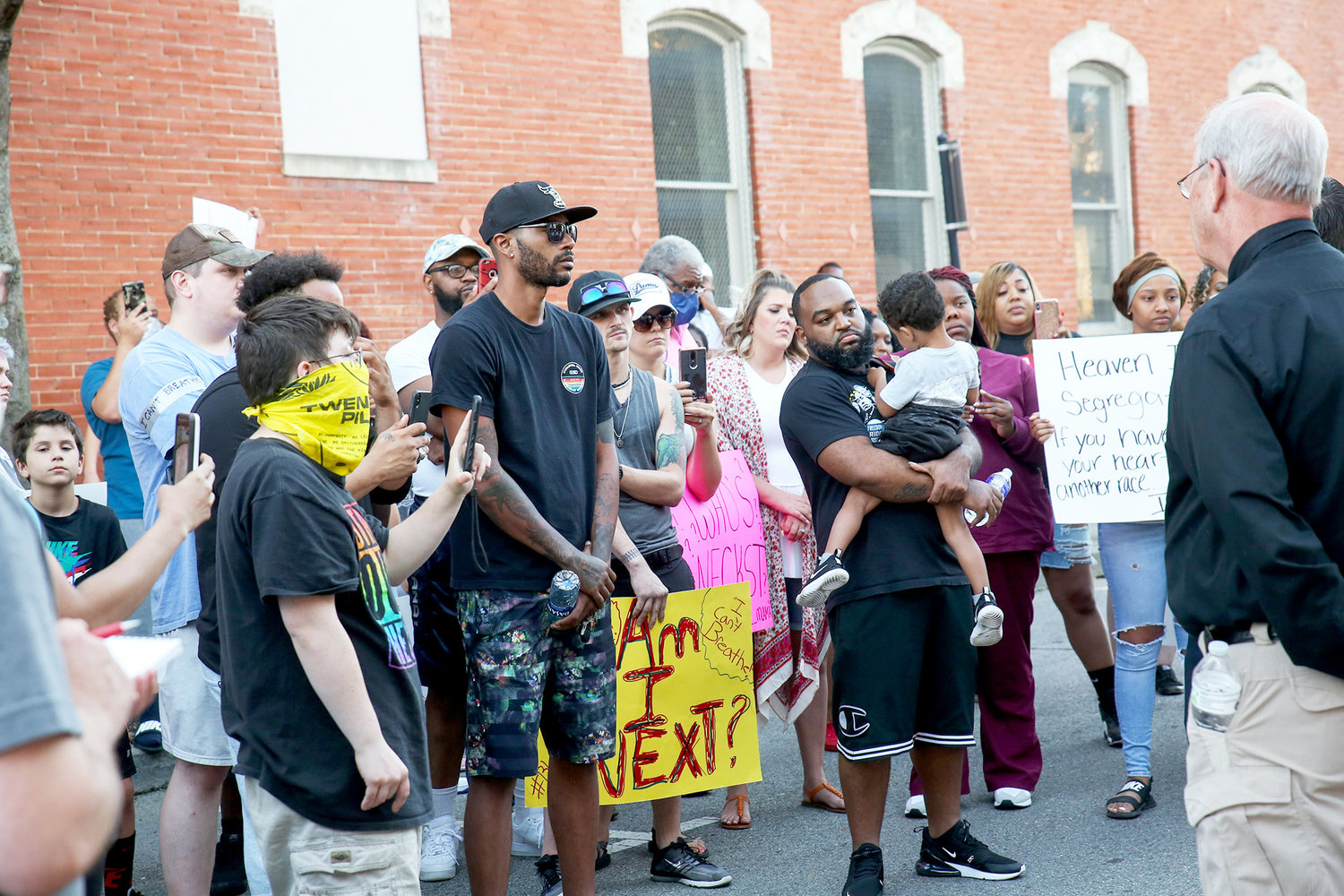 PROTESTERS LISTEN WHILE CPD Chief Mark Gibson, not pictured, and Sheriff Steve Lawson speak to the crowd assembled on Church Street on Sunday.