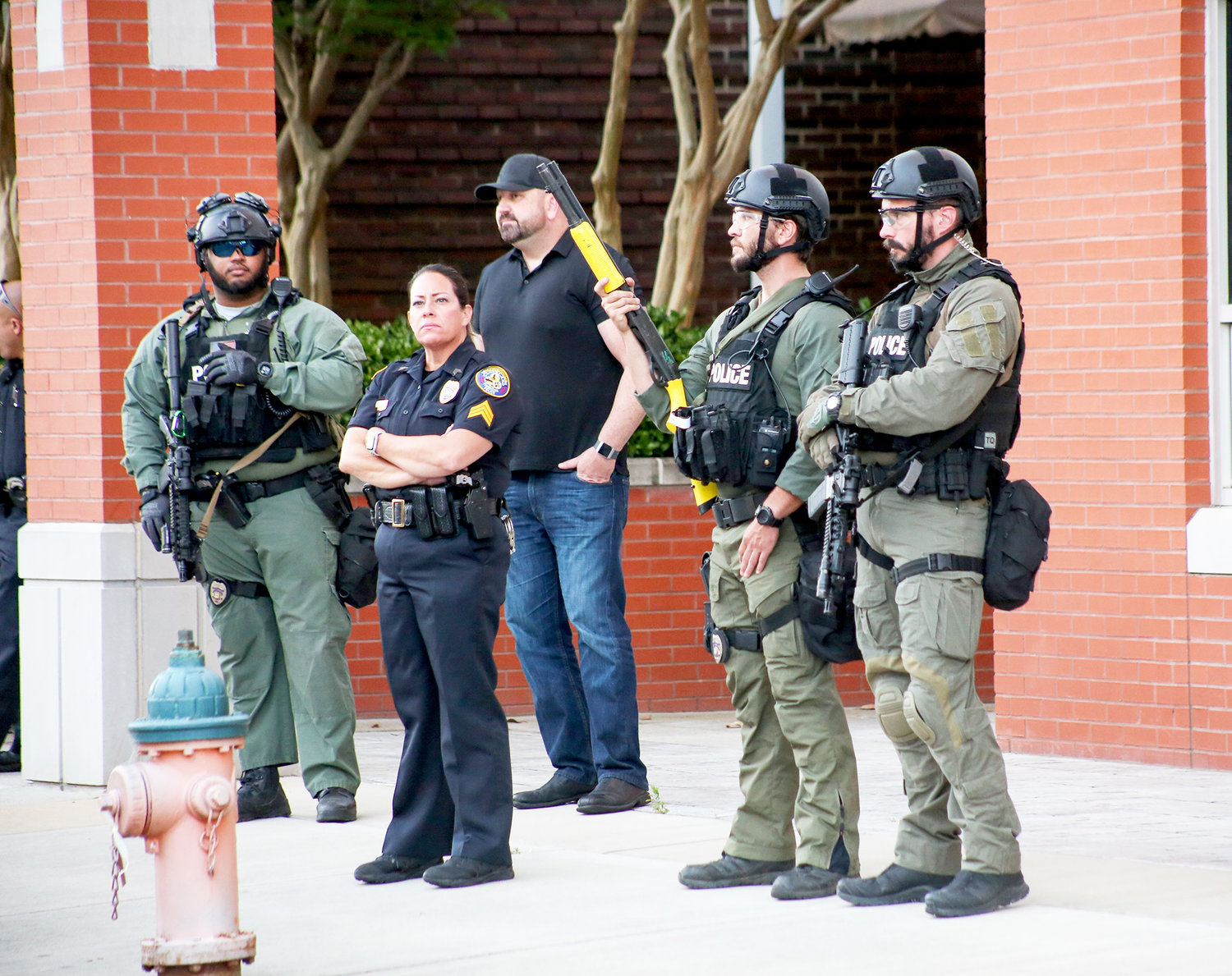 PUBLIC INFORMATION OFFICER Evie West, center, and fellow officers in tactical gear stand in front of the Cleveland Police Department during Sunday's protest.