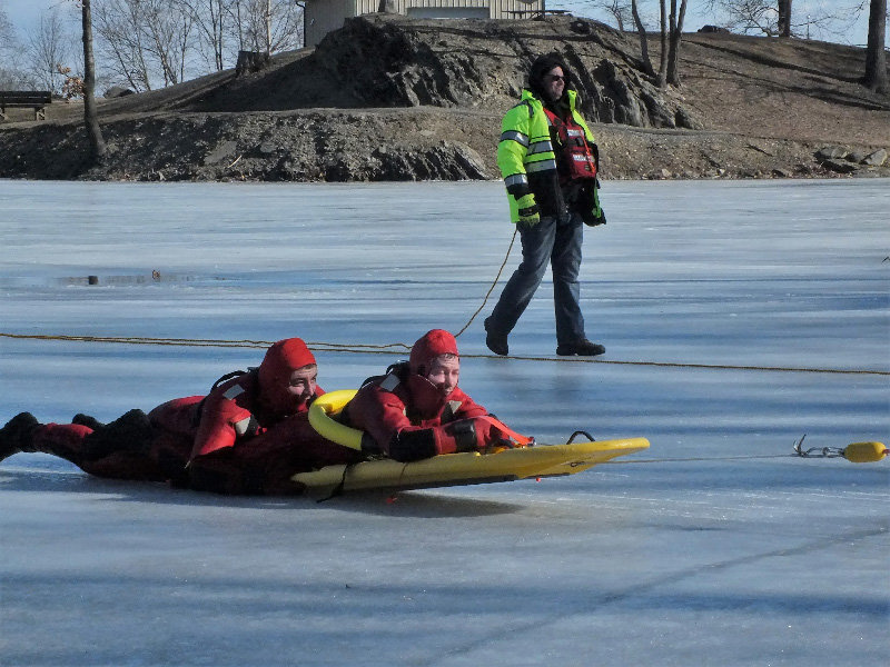 Paul DeAngelis rides out on a rescue sled to help Cory Rhynehart in the water, while Assistant Chief Lenny Scaturro supervises.