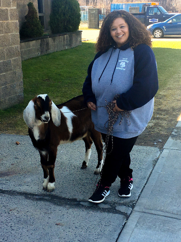 Maritza stands outside the Recreational Center with her pet goat Buddy.