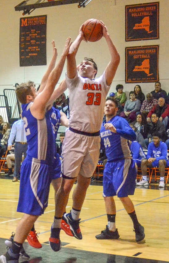 Marlboro's A.J. Musacchio goes up for a shot as Wallkill's Paul Shea defends during Friday's MHAL boys' basketball game at Marlboro High School.