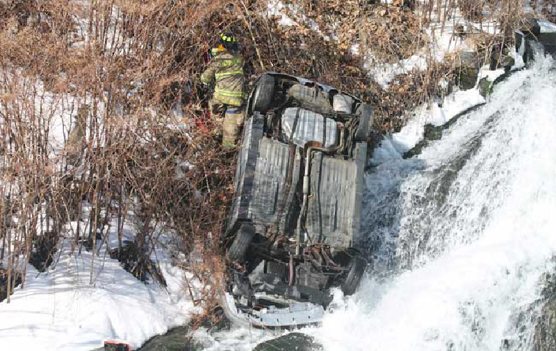 A Marlboro firefighter examines a car that had been pushed over an embankment along Route 9W last week.