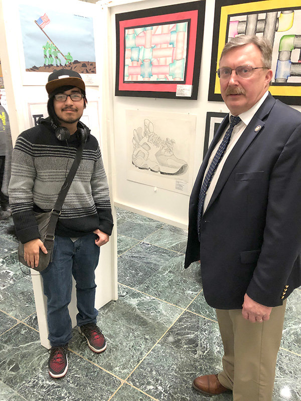 "Assemblyman Brian Miller and Demian Martinez Genis pose next to Martinez's pencil drawing, ""Sneaker,"" now on display in the Legislative Office Building in Albany."