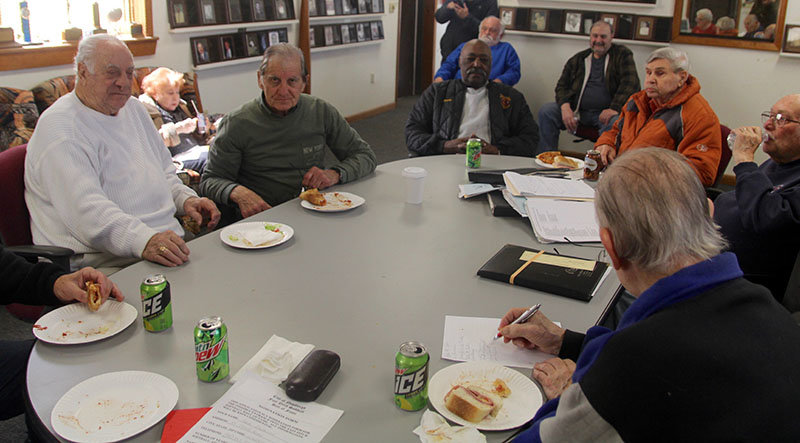 Members gather once a month for a meeting, which is preceded by a lunch of ballpark food such as soda, pizza and subs.