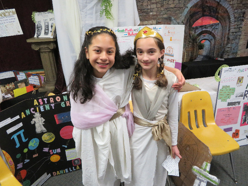 Daniella (left) and Amelia, fifth-grade students, present facts on Greek astronomy and science.