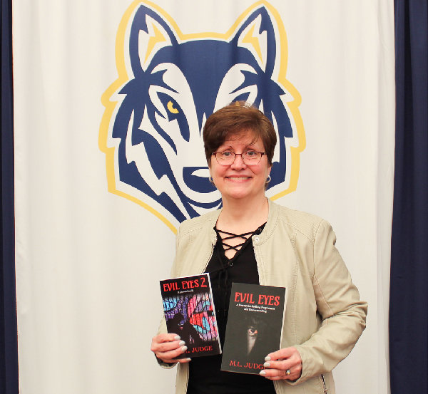 """Mikki Judge shows her Husky pride as she poses in the Highland High School Library Media Center with her books """"Evil Eyes: A Journey in Seeking Forgiveness and Understanding"""" and """"Evil Eyes 2: A Chosen Family."""""""
