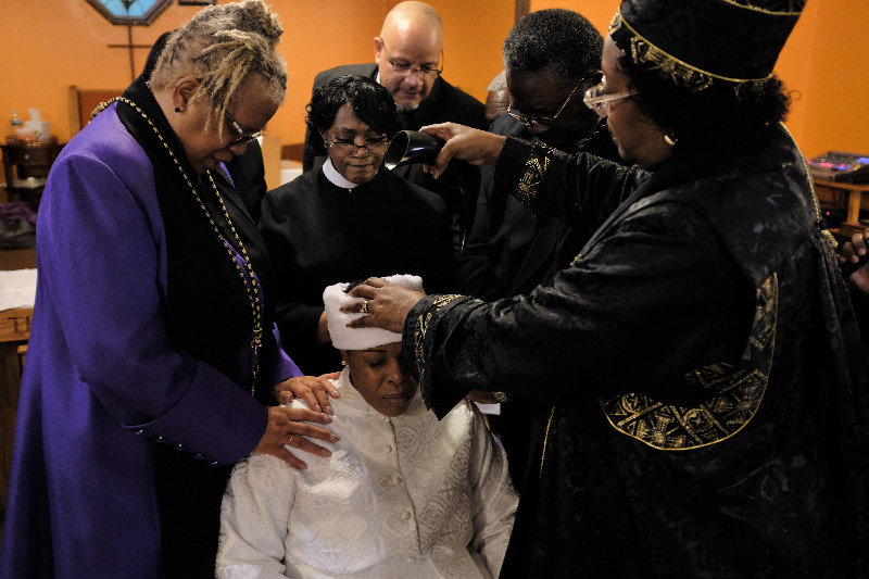 Oil is poured over Monique K. Newkirk's head as part of the installation ceremony.