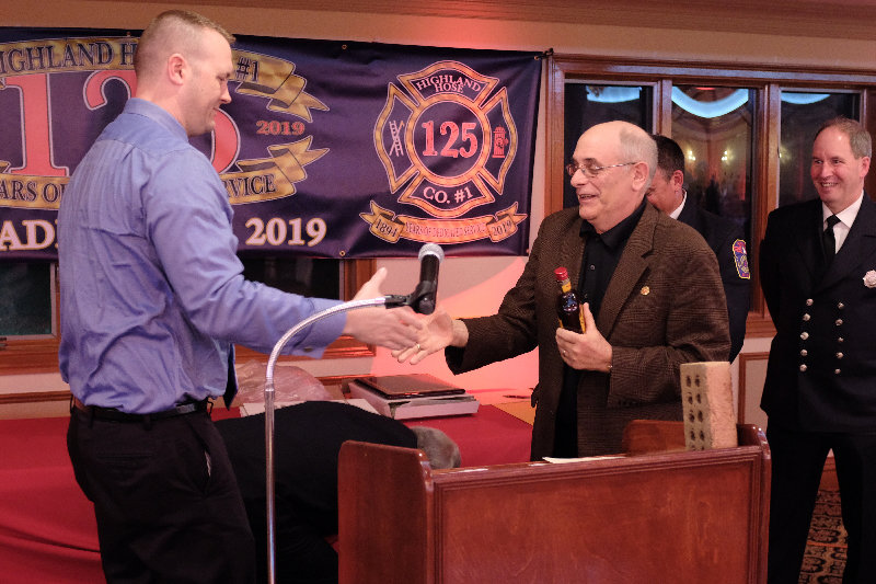 "At the Highland Fire Company's annual installation dinner in May, Lloyd Police Sgt. Phil Roloson [L] teases Stephen DiLorenzo by presenting him with a 'Fireball"" cordial that he won but failed to take home after a Red Cross fundraising diner."