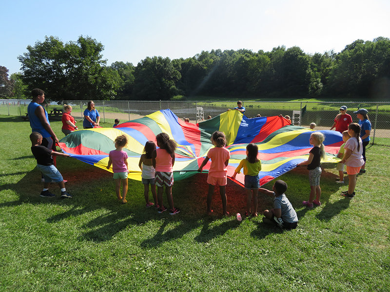 Children play games with a tarp at the Village of Walden's summer camp. The program enrolled about 300 children this year, down slightly from previous years. Photo by Laura Fitzgerald.