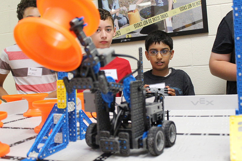"Kyle Menezes, from the Highland Central School District, moves a ""hub"" with his VEX robot at the Ulster BOCES Nuts, Bolts & Thingamajigs Robotics Camp."