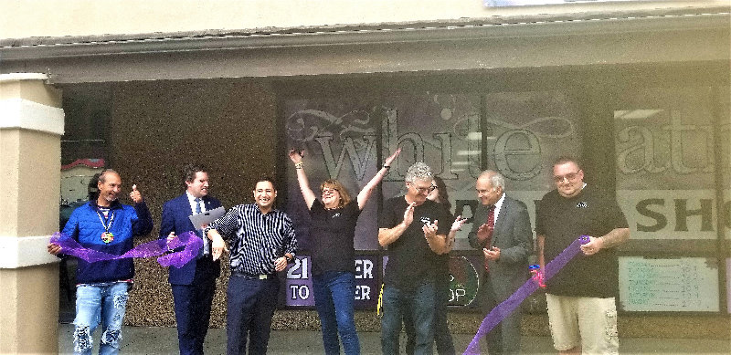 Kimberly Sanders-Eachus cuts open the purple ribbon to commemorate the grand opening of the White Atmoss Vape & CBD Shop.