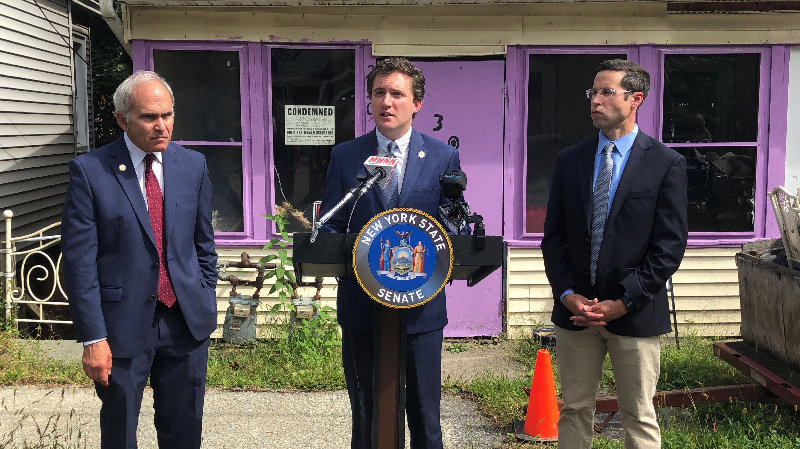 State Sen. James Skoufis (c)  speaks at the center with Assemblyman Jonathan Jacobson on the left and Assemblyman Ken Zebrowski on the right.