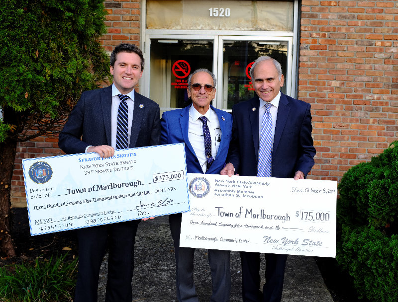 Marlborough Supervisor Al Lanzetta (center) accepts checks totaling $550,000 from NYS Sen. James Skoufis (L) and NYS Assemblyman Jonathan Jacobson that will be used to renovate the TOMVAC building.
