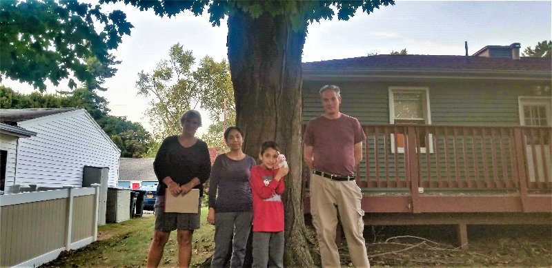 From left to right, Barbara Knoezer (Grant Miller's neighbor at 29 Hilltop Drive), Luz Miller (Grant Miller's wife), Grant MillerJr., and Grant Miller stand in the backyard of 27 Hilltop Drive.