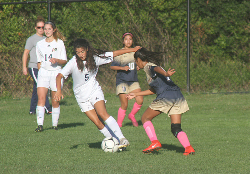 Pine Bush girls were blanked 3-0 in a game at Newburgh Free Academy on Oct. 10. Pictured (l. - r.) Angelina Cardone (5) of Pine Bush battles a Newburgh player for control of the ball.