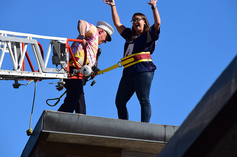 A staff member waves from the roof as she is helped by a Cronomer Valley Fire Fighter.