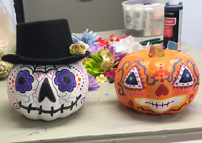 Two pumpkins that were painted at the Day of the Dead pumpkin painting event.