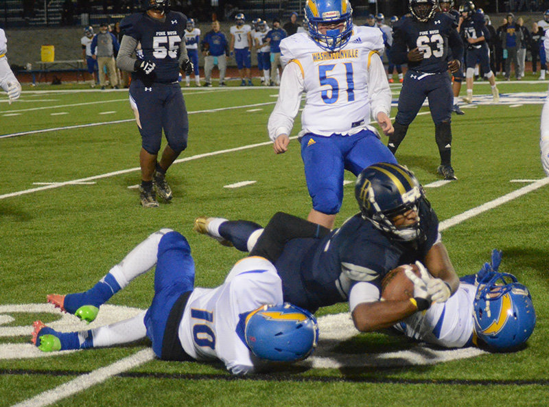 Pine Bush's David Alcenat dives for extra yards as he is brought down by Washingtonville's William Cooper and Ryan Hendricks during Saturday's Section 9 Class AA semifinal football game at Faller Field in Middletown.