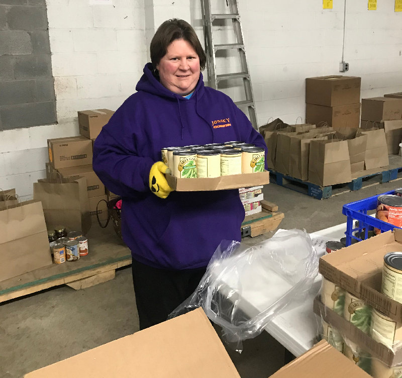 Karena Winum  packs cans of green beans for the Thanksgiving gift baskets.