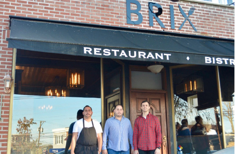 Owners of the Brix Gastropub, (l – r.)  Frank Harpolis, Teddy Harpolis and Dane DeSantis in front of their restaurant.