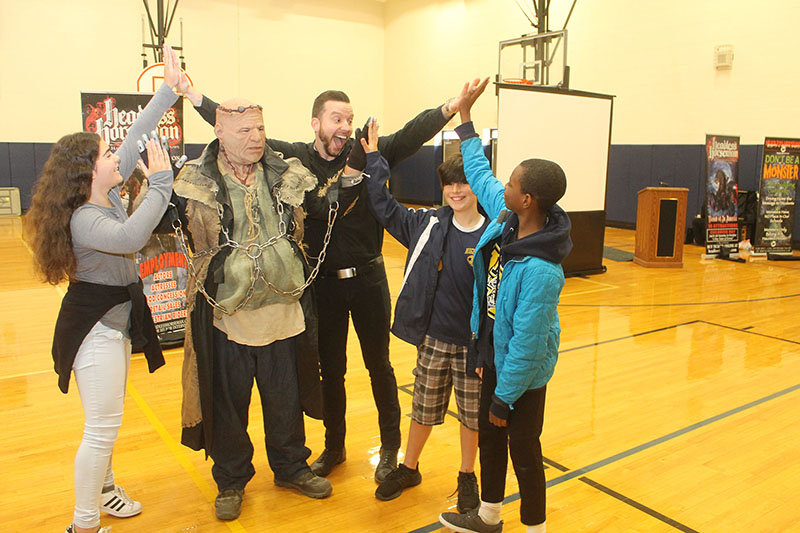 """At the conclusion of the recent """"Don't Be A Monster"""" anti-bullying program, illusionist and presenter from the Headless Horseman company Ryan Dutcher and Frank Shelley share some """"high fives"""" with HMS students (l.-r.) Eva Meyer, Basil Metz, and Cameron Adoma."""