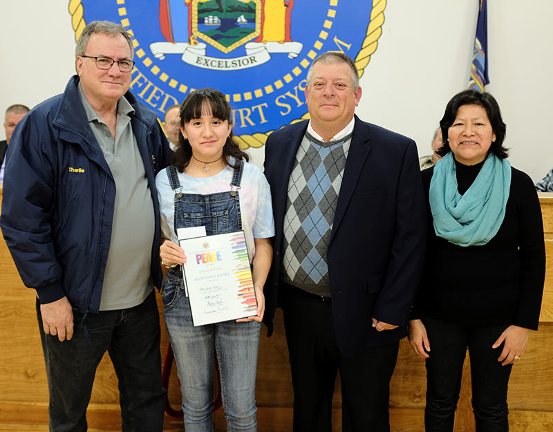 Student artist Charlene Kanz stands beside her father Charles (L), Lions Club representative Ed Mackey Jr and mother Jovita Kanz.