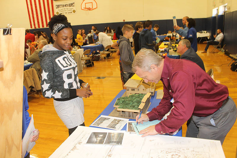 During the recent Highland Middle School (HMS) Career Day event, HMS student Janelle Landell chatted with architect Dave Toder about the finer points of the field of architecture, as he demonstrated using the small-scale model buildings he created during his professional education.