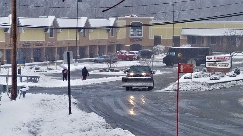A snow plow truck drives out of the Thruway Shopping Center in Walden on Monday morning.