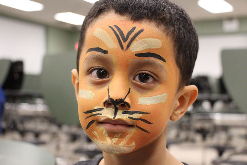 Mario Osorto Zuniga, a kindergarten student at CES, sat patiently to be transformed into a tiger at the face-painting table.