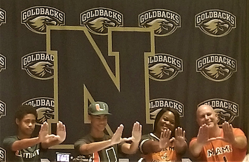 Ryler Gould and his family make University of Miami hand symbols.