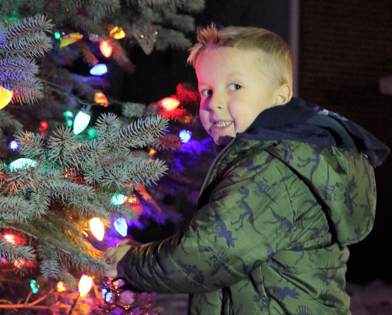 Gary Call III adds his ornament to the lit tree.