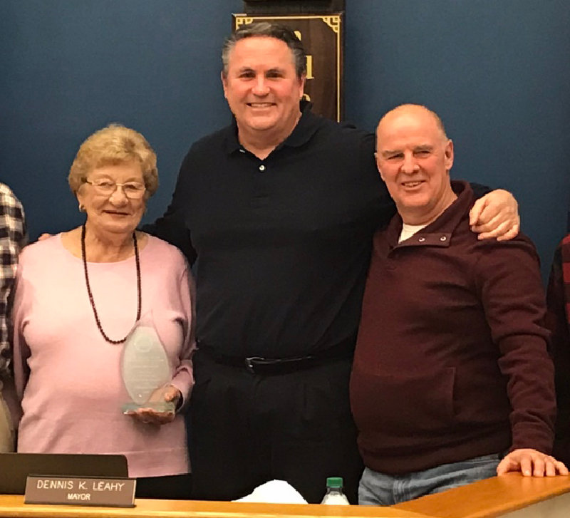 Jane Schimpf (left) holds the 2019 Joseph E. Dineen Award with Mayor Dennis Leahy (center) and Deputy Mayor Robert Pritchard (right).