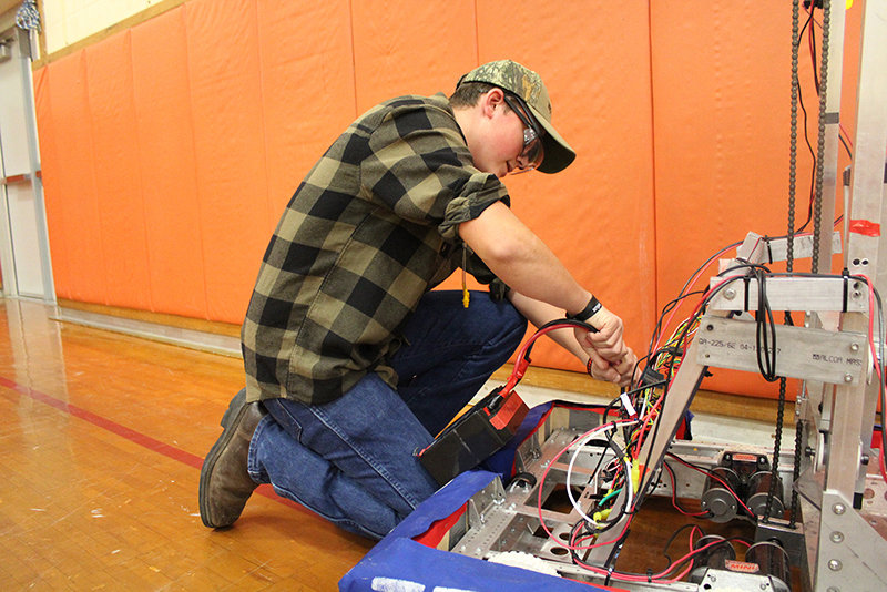 Hudson Valley Pathways Academy (HVPA) student Benjamin Dubois, from the Highland Central School District, replaces the battery in an industrial-size robot during a robot competition at HVPA.