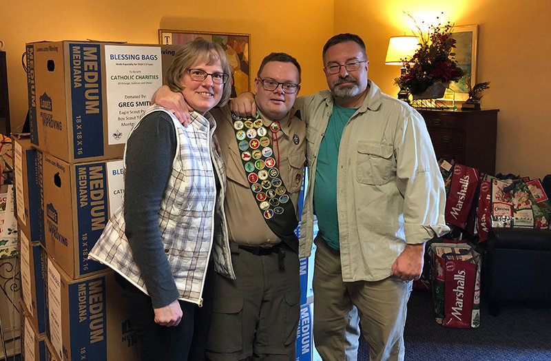 "Montgomery Boy Scout, Greg Smith, a member of Troop 386, selected Catholic Charities to be the beneficiary of his Eagle Scout project. He is pictured with his parents, Heidi and Rick, delivering the 210 ""blessing"" bags that were prepared for Catholic Charities."