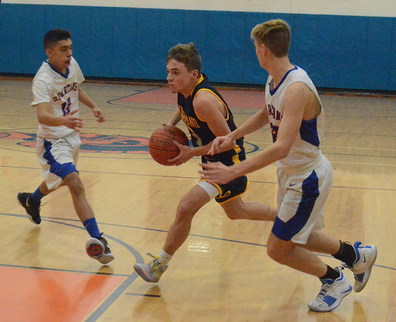 Highland's Deryk Barry drives the lane as S.S. Seward's Gavin Acuna and Shawn Behrent defend during Friday's John Guerra Memorial Spartan Invitational consolation boys' basketball game at the S.S. Seward Institute in Florida.
