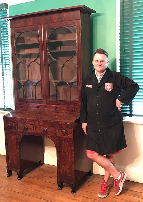 Christopher Anigacz, founder and sole employee of Double Queue, stands next to a finished piece of furniture.