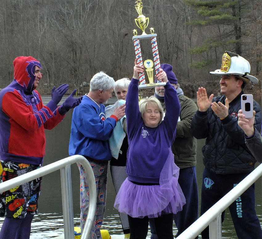 Leslie Benson, of the Highland Ladies Auxiliary, holds high the 1st Place trophy in fundraising that was won by Team Ulster County Firefighter.