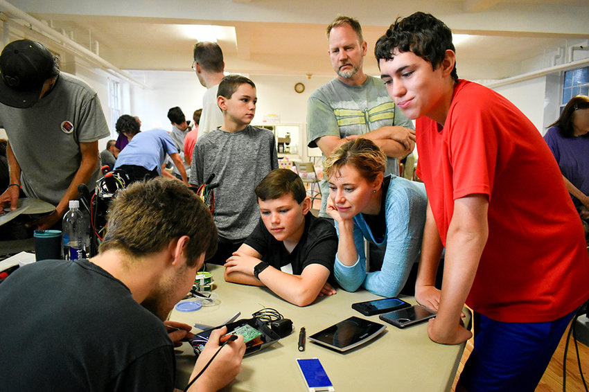 Marcy Cleveland (second from right) and Jeff Luoma (background) look at an appliance being fixed at Repair Café New Paltz with Cleveland's three sons (from left to right: Grant, Henry and Nolan Brown).