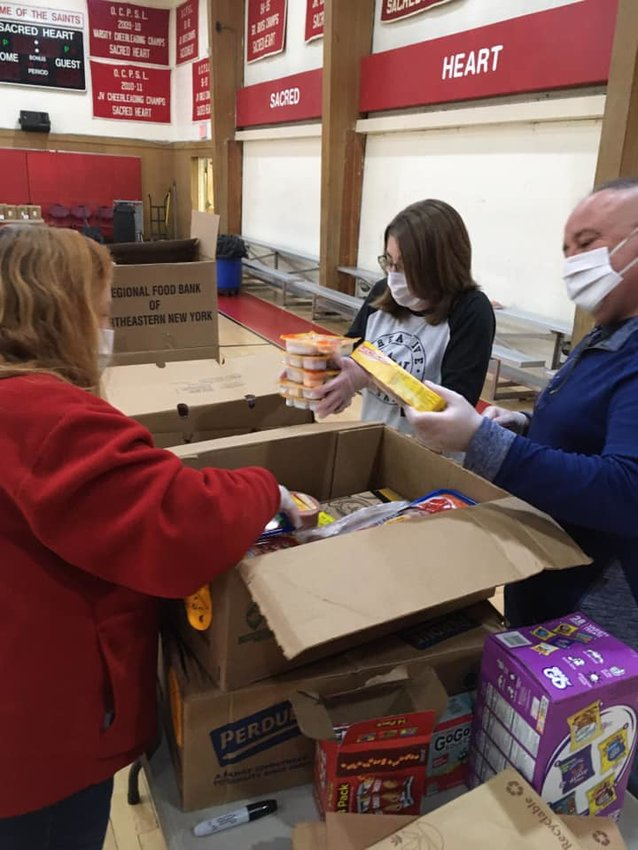 Sacred Heart Parish Outreach volunteers packing food to be delivered to those in need.