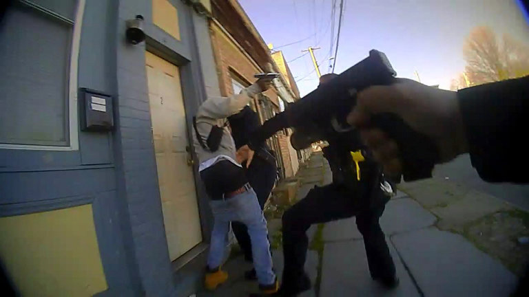 The Orange County District Attorney's office released a still photo from a police body cam showing a suspect with what appears to be a gun, surrounded by police officers.